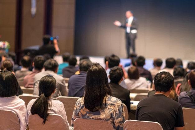 rear side audiences sitting listening speackers stage 41418 2175 min 1 - ¿Cuál es el protocolo de eventos empresariales?